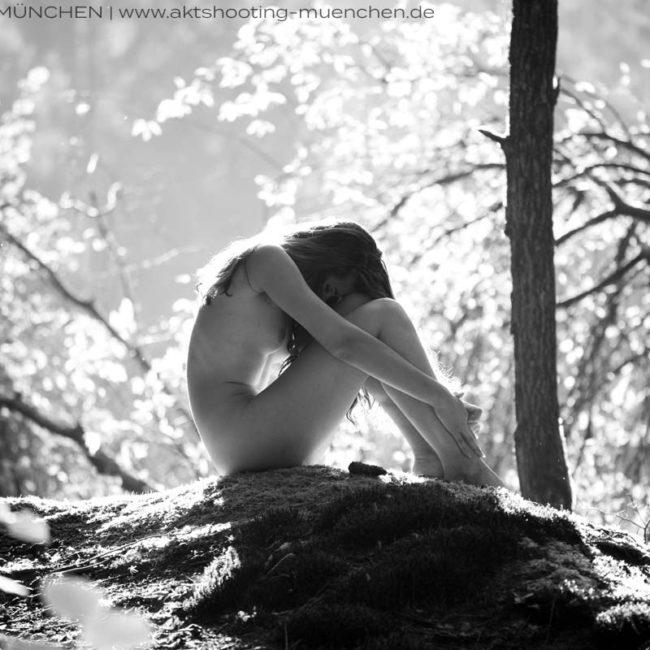 Akt in der Natur, Frau sitzt in Waldlichtung bei Aktshooting in München