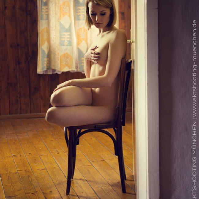 Aktfoto von Frau auf Holzstuhl bei Homeshooting in München