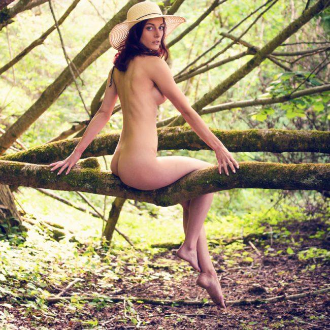 Aktfoto München von Frau auf Baumstamm