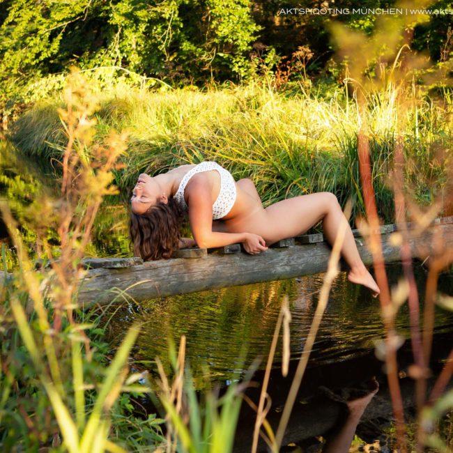 Aktfoto München, Model liegt auf der Brücke am See
